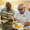 Globe/Roger Nomer<br /> Eddie Gonzalez, ESL teacher with Crowder, right, shows Tarig Mohamed the traditional Thanksgiving usage of gravy on Monday at the Noel Community Center.