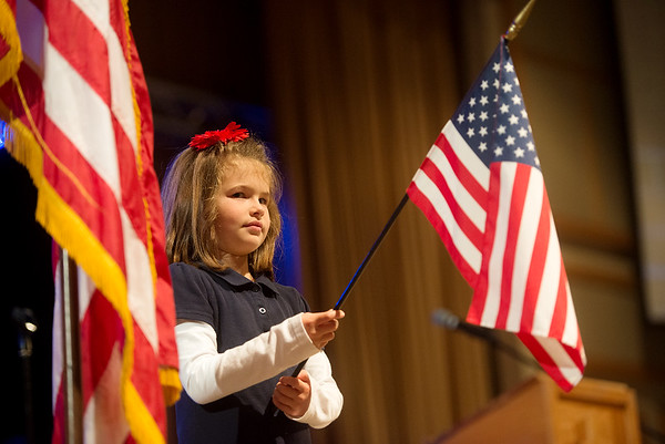 Globe/Roger Nomer<br /> Izzie Morris, College Heights first grader, holds a flag for the Pledge of Allegiance during Thursday's ceremony at the school.