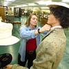 Pittsburg State Circle K Vice President Ailee Story straightens the collar on the blouse worn by a 1940s era mannequin on Thursday at the museum. <br /> Globe | Laurie SIsk