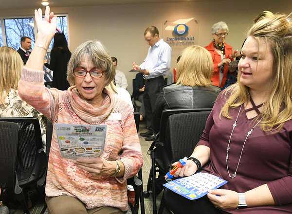 From the left: Bonnie Pefferman, of Lancaster Signs, raises her hand with a winning Bingo as Chrissy McKee, of the Peregrine Corporation looks on during the Joplin Area Chamber of Commerce combined 100th Birthday, Member Appreciation Party and Holiday Open House on Wednesday at the Chamber. Pefferman was awarded a 40-inch television with her winning Bingo.<br /> Globe | Laurie Sisk
