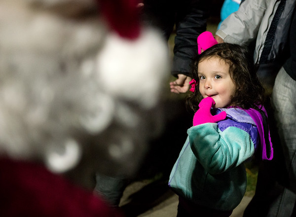 Nora Shead, 2, catches a glimpse of Santa before Tuesday's Christmas tree lighting in Spiva Park.<br /> Globe   Roger Nomer