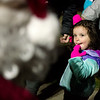 Nora Shead, 2, catches a glimpse of Santa before Tuesday's Christmas tree lighting in Spiva Park.<br /> Globe | Roger Nomer
