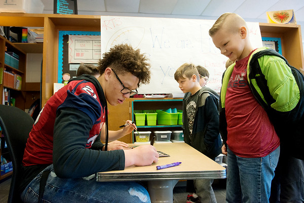 Isaiah Davis, a Joplin High junior, signs an autograph fro Grayson Heritage, a third grader at Kelsey Norman on Friday.<br /> Globe | Roger Nomer