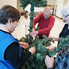 (from left) Mercy Hospital Joplin Volunteer Services members Beverly Newman, Don Scott, Charimonde Heger and Doc Edwards set up a giving tree at the hospital on last Friday. Guests of the hospital and those in need will be able to take hats, socks, gloves and other useful items from the giving trees. People will also be able to leave new supplies on the trees when they visit the hospital.<br /> Photo Submitted by Mercy Hospital