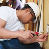 Alexter Montojo, a transfer freshman at Pittsburg State from Fort Scott, replaces an outlet at the Ronald McDonald House of the Four States on Wednesday. Students from PSU's electrical engineering program volunteered at the house making upgrades and renovations to its electrical system.<br /> Globe | Roger Nomer