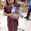 Nayeli Vasquez-Yac, third grader at Columbian Elementary in Carthage, holds a book about a Guatemalan girl who weaves dresses as she wears the dress she wove. Vasquez-Yac is part of the 70 percent Hispanic population at the school and is herself Guatemala.<br /> Courtesy Photo/Kim Meyer