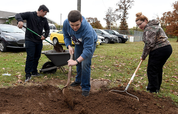 From the left: Crowder College students Keller Wilson, Jonathan Blewett and Stormy Tramell shovel dirt to fill holes in the grounds at the Faithful Friends animal shelter on Saturday in Neosho. About 60 volunteer students completed a variety of tasks Saturday at the shelter.<br /> Globe   Laurie SIsk
