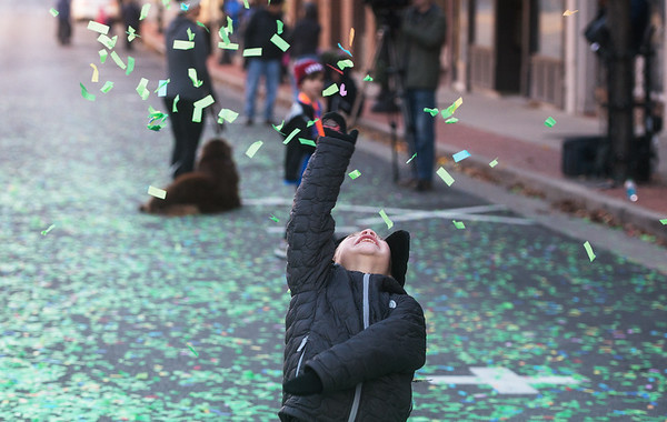 Aiden Bennett, 6, Joplin, plays in the confetti while waiting for his parents to cross the finish line at the Turkey Trot 5K on Thursday in downtown Joplin.<br /> Globe | Roger Nomer