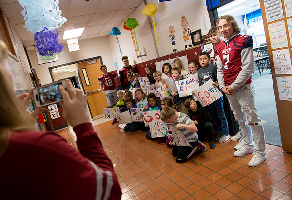 Joplin High football players pose for photos with Kelsey Norman third graders on Friday.<br /> Globe | Roger Nomer