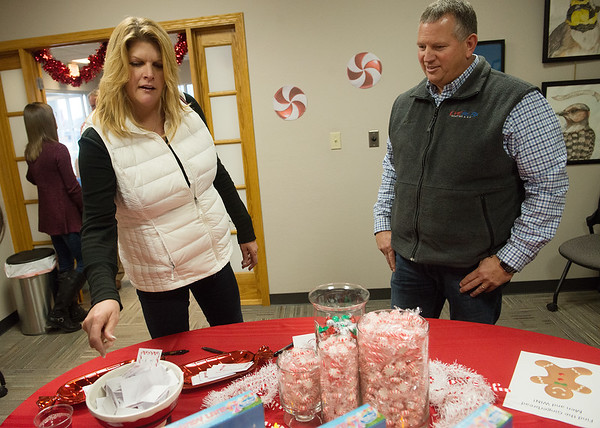 Kim and Kevin Brady make their guesses on the number of candy pieces in a jar during Friday's Holiday Open House at the Joplin Area Chamber of Commerce.<br /> Globe | Roger Nomer