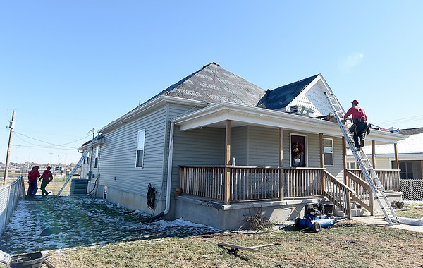 A crew from Mayberry Roofing helps install new roofing donated by Tamko on a house in South Joplin on Tuesday.<br /> Globe | Laurie Sisk