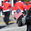 A spectator holds a U.S. flag as a band marches by during the 31st Annual Veteran's Day Parade on Saturday morning in downtown Joplin.<br /> Globe | Laurie Sisk