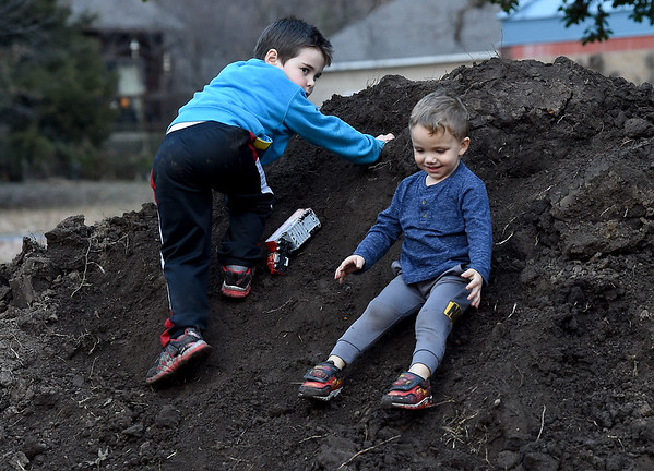 From the left: Eli Forsythe, 6 and Roman Webb, 3, slide down the side of a large mound of dirt as they have a little good, clean fun on a warm day at Pittsburg's Lakeside Park on Thursday.<br /> Globe | Laurie Sisk