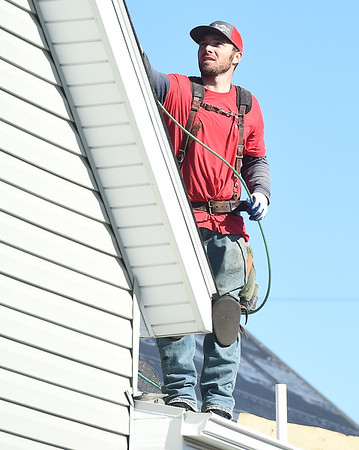 Austin Lamb, of Mayberry Roofing, helps install new roofing donated by Tamko on a house in South Joplin on Tuesday.<br /> Globe | Laurie Sisk