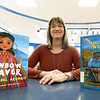Kim Meyer, media center specialist at Columbian Elementary in Carthage, poses with two of the several books she has incorporated into the school's library to reflect the 70 percent hispanic population of the school.<br /> Globe | Laurie Sisk