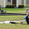 An investigator with the Missouri Highway Patrol places evidence markers at the scene of an officer-involved shooting early Friday afternoon in the playground of the Springhill Apartments near 21st and McCoy streets.<br /> Globe   Laurie Sisk