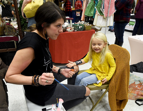 Sarah Eidson, left, applies a glittr unicorn on the arm of 4-year-old Sailor Benfield during the 32nd Annual Cecil Floyd craft Show on Saturday at the school. Eidson was helping her 11-year-old daughter, Londyn Eidson, who developed the concept for the Lou Glitter Co. booth.<br /> Globe | Laurie Sisk