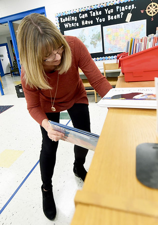 Kim Meyer, media center specialist at Columbian Elementary in Carthage, shelevs books on Tuesday the school's library. Meyer has worked to add books that reflect the 70 percent hispanic population of the school.<br /> Globe | Laurie Sisk