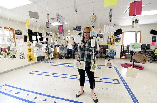 "Freshman Krista Skinkis checks out an art installation piece entitled ""Visions,"" created by Crowder-Cassville art instructor Leigh Wallace. The piece, inside the adminstration building at Crowder-Cassville, features about 150 postcards from around the globe, suspended by string in an interactive design.<br /> Globe 