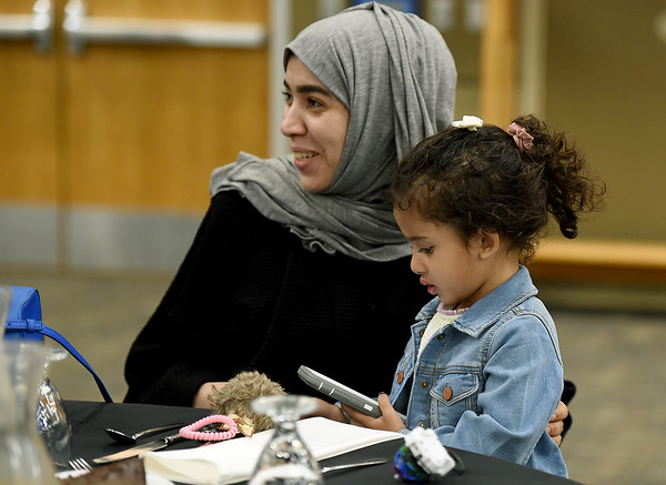 Saudi Arabian chemistry major May Altammar visits with fellow Pittsburg State international students as her daughter, Latifah Alowaise, 4,  occupies herself with a cell phone during PSU's end of semester banquet for international students on Thursday night at PSU.<br /> Globe | Laurie Sisk
