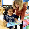 Kim Meyer, media center specialist at Columbian Elementary in Carthage, helps first grader Anayensi De Leon select a book on Tuesday at the school's library. Meyer has worked to diversify the library to reflect the 70 percent hispanic population of the school.<br /> Globe | Laurie Sisk