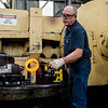 Tom Bishop works with hot metal bearings in the forge at Schaffler on Oct. 30.<br /> Globe | Roger Nomer