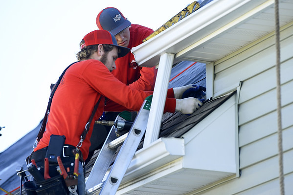 From the left: milton Lamb and Tavis Laub Milton Lamb, of Mayberry Roofing, install new roofing donated by Tamko on a house in South Joplin on Tuesday.<br /> Globe | Laurie Sisk