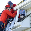 From the left: milton Lamb and Tavis Laub Milton Lamb, of Mayberry Roofing, install new roofing donated by Tamko on a house in South Joplin on Tuesday.<br /> Globe   Laurie Sisk