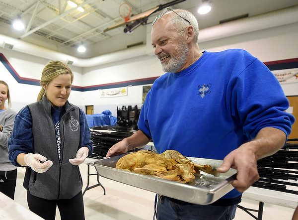Salvation Army cook Rusty Long delivers one of 25 turkeys to Missouri Southern Zeta Tau Alpha sorority sister Abbey Elmore for deboning on Thursday night at the Salvation Army. Elmore has volunteered for Thanksgiving food prep for the last four years and joined 51 of her other sisters in helping to feed a projected 400 to 500 guests on Thanksgiving Day.<br /> Globe | Laurie Sisk