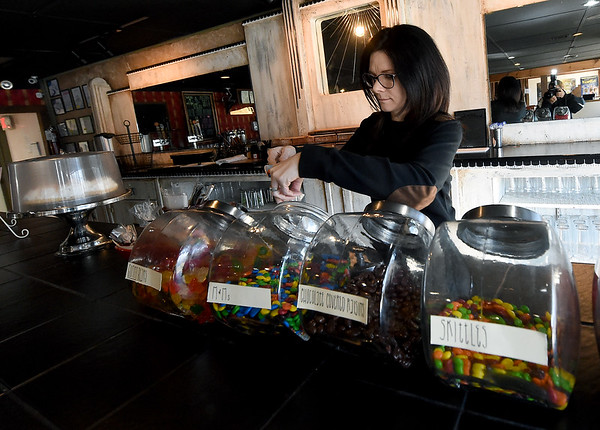 Holly Crane restocks candy in the lobby of Bookhouse Cinema, which she and her husband, Brad Carne opened earlier this year.<br /> Globe | Laurie Sisk