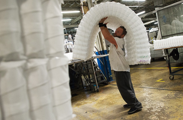 Randy Ralston, material handler at Leggett and Platt, works with mattress coils on Friday at the plant in Carthage.<br /> Globe | Roger Nomer