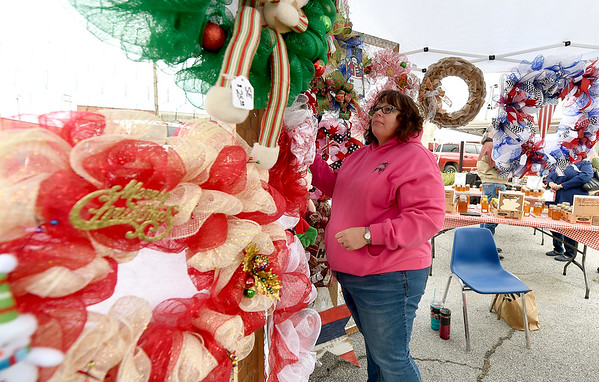 Carrie Moore, of Crafter's Log, arranges colorful custom made wreaths inside her booth during the Handmade Holiday Market on Saturday at the Neosho Farmers Market.<br /> Globe   Laurie SIsk