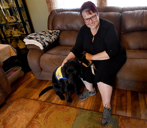 Mary Green poses with Declan III, a labrador retriver that she and her daughter Kyna Adams are training as a service dog through Canine Companions.<br /> Globe   Laurie SIsk