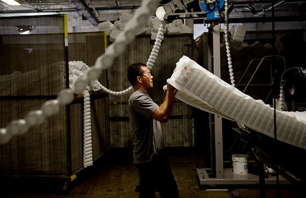 Olmen Contreras, machine operator at Leggett and Platt works with mattress coils on Friday at the plant in Carthage.<br /> Globe | Roger Nomer
