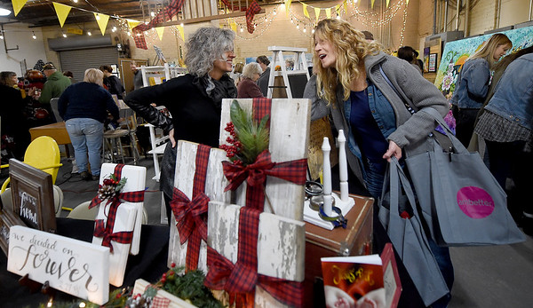 From the left: Tiffany Thompson, of Tattoos by Tiffany, chats with Jody Berry, of Baxter Springs, during the Hip Handmade Market on Saturday at the Empire Market. Thompson, who specializes in henna tattoos, decided to bring a little Christmas into her booth on Saturday.<br /> Globe | Laurie Sisk
