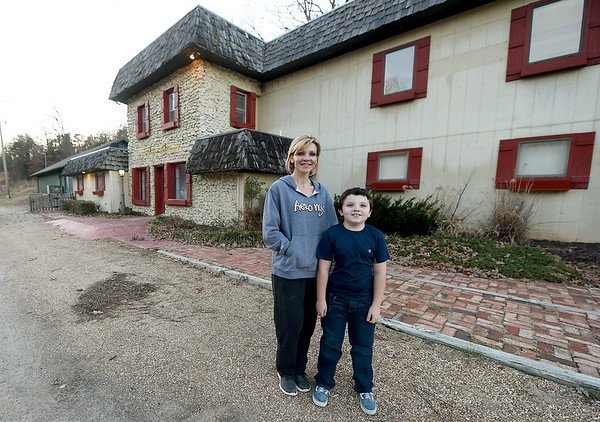Stacia Elliott and her son, Tate Elliott, stand outside the old Richardson's Candy House on Tuesday. Elliott plans to open a medical spa and other businesses inside the historic building, while keeping some artifacts from the candy house.<br /> Globe | Laurie Sisk