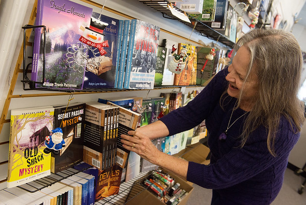 Susie Davidson arranges the local author section of Changing Hands Book Shoppe on Friday afternoon.<br /> Globe   Roger Nomer
