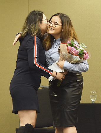 Pittsburg State international student Dilara Maihemuti, right, receives a bouquet and a hug from fellow classmate and international student from Northwest China Gulifeila Alimu at PSU's end of semester banquet for international students on Thursday night at PSU.<br /> Globe | Laurie Sisk
