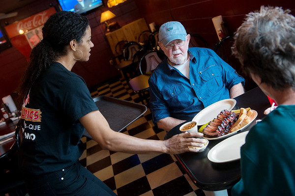 Florida serves Earl Curry, Joplin, an order on Thursday at Little Pigs Barbecue.<br /> Globe   Roger Nomer