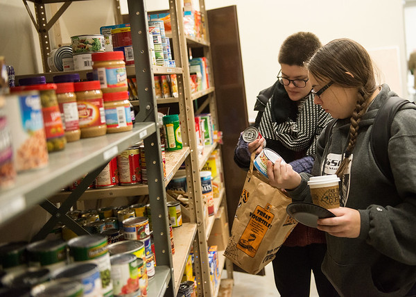 Mikaela Walker, human resources assistant at the Missouri Southern Gold Program, left, and Debbie Davis, a MSSU sophomore from Cassville, donate food to the Lion Co-Op food pantry on Tuesday.<br /> Globe | Roger Nomer