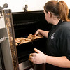 Jessica Coffey-Scott, head chef, puts chicken in a smoker at Little Pigs Barbecue on Thursday.<br /> Globe | Roger Nomer