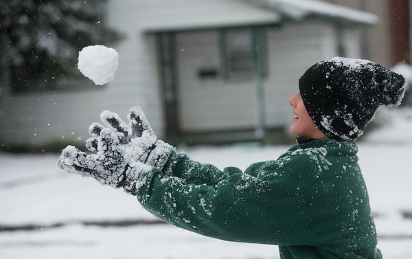 Levi Arias, 12, tosses a snowball in the air while playing with his family in Webb City on Monday. Globe | Roger Nomer