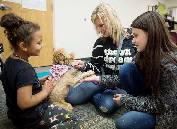 (from left) Jayla Wyatt, first grader at Royal Heights Elementary, Nasha Robinson, school counselor, and Lilah North, third grader, play with Bridget on Tuesday at the school.<br /> Globe | Roger Nomer