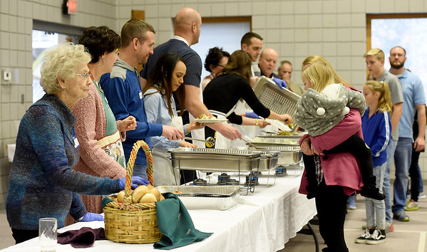 Volunteers serve some of the 500 expected guests during the community Thanksgiving dinner on Thursday at First United Methodist Church. <br /> Globe | Laurie Sisk