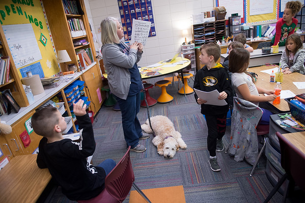 Kate Tupper holds Maple's leash while instructing her second-grade students on an exercise on Tuesday at Royal Heights Elementary.<br /> Globe | Roger Nomer
