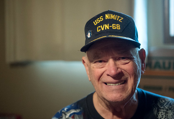 Ron Mosbaugh wears a hat he received from the USS Nimitz at his home on Thursday.<br /> Globe | Roger Nomer