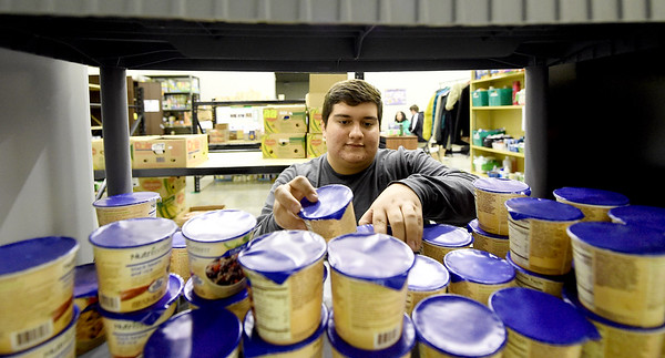 Missouri Southern Social Work intern Gil Salgado stocks shelves inside the Lion Co-op on Wednesday. The co-op, formed last year, is starting a new program called Adopt A Lion, in which donors may sponsor a lion throughout the month of December to ensure that they'll have food over Christmas break.<br /> Globe | Laurie Sisk