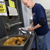 Salvation Army chef Rusty Long unwraps one of 32 turkeys that will be served for the Salvation Army's annual Thanksgiving dinner. <br /> Globe | Laurie SIsk