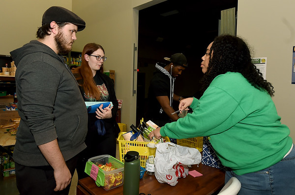 Chrislynn Powers, left, assists shoppers Tristan Wood, left and Dylan Duvall as they shop at the Lion Co-op on Wednesday. The co-op, formed last year, is starting a new program called Adopt A Lion, in which donors may sponsor a lion throughout the month of December to ensure that they'll have food over Christmas break.<br /> Globe | Laurie Sisk