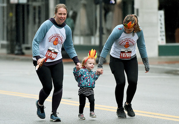 Amelia Thach, who turns two next month, smiles as she runs the course with her mom, Christy Thach, left and aunt, Lauren Burleigh during the 8th Annual Joplin Turkey Trot on Saturday in downtown Joplin. <br /> Globe | Laurie Sisk